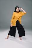 Elegancki atrakcyjny model pozuje w żółtej bluzce i czarnych szerokich spodniach Obraz Stock