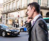 Elegancki biznesmenów wp8lywy telefon komórkowy wzywał Paryską ulicę Zdjęcia Stock