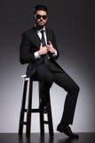 Elegancki biznesowy mężczyzna jest ubranym czarnych okulary przeciwsłonecznych załatwia jego kurtkę zdjęcia royalty free