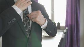 Elegancki biznesowy mężczyzna koryguje jego w białej koszula krawat zdjęcie wideo