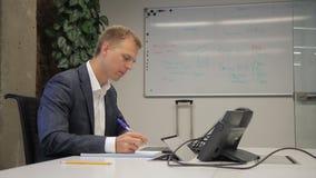 Elegancki biznesowy mężczyzna pisze notatkach w notatniku i działaniu na laptopie zbiory wideo