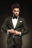 Elegancki biznesowy mężczyzna układa jego smoking Obrazy Royalty Free