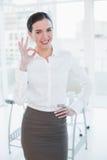 Elegancki bizneswoman gestykuluje ok podpisuje wewnątrz biuro Fotografia Royalty Free