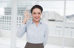 Elegancki bizneswoman gestykuluje ok podpisuje wewnątrz biuro Zdjęcie Stock