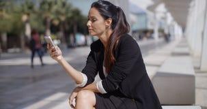Elegancki bizneswoman sprawdza jej telefon wiadomości obrazy stock