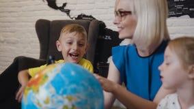 Elegancki blondynka nauczyciel pokazuje uczniom kulę ziemską na geografii lekci Nauczyciel dyskutuje a z dwa dzieci zabawą zdjęcie wideo