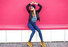 Elegancki blondynki dziewczyny model w długiej pozuje jest ubranym rockowej czerń stylu kurtce, kapelusz na miasto ulicie nad kol zdjęcie royalty free