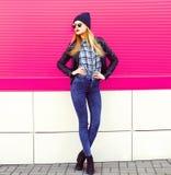 Elegancki blondynki kobiety model w długiej pozuje jest ubranym rockowej czerń stylu kurtce, kapelusz na miasto ulicie nad koloro obrazy royalty free