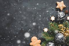Elegancki Bożenarodzeniowy tło z spada śniegiem, rocznik zabawkami, jedlinowym drzewem i ciastkami na czerń kamieniu, zdjęcia stock