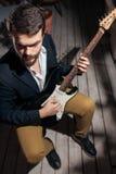 Elegancki brodaty mężczyzna z gitarą elektryczną; obrazy royalty free