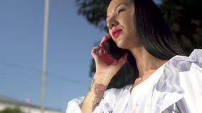 Elegancki Brunete z czerwoną pomadką opowiada na telefonie przeciw niebu zbiory wideo