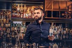 Elegancki brutalny barman w czarnej koszula przedstawia butelkę wyłączny alkohol przy baru kontuaru tłem zdjęcie royalty free