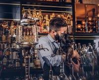 Elegancki brutalny barman w koszula i fartucha utrzymań thoroughbred czerni mopsie przy barem sprzeciwia się tło obrazy stock