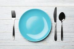 Elegancki ceramiczny talerz i cutlery na białym drewnianym tle obraz stock