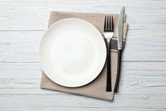 Elegancki ceramiczny talerz, pielucha i cutlery na białym drewnianym tle, zdjęcie stock