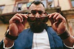 Elegancki chłodno brodaty mężczyzna bierze daleko jego szkła Obraz Stock