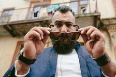 Elegancki chłodno brodaty mężczyzna bierze daleko jego szkła Fotografia Stock