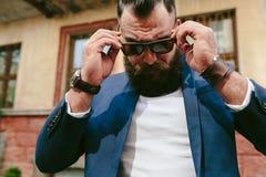 Elegancki chłodno brodaty mężczyzna bierze daleko jego szkła Zdjęcia Stock