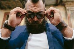 Elegancki chłodno brodaty mężczyzna bierze daleko jego szkła Zdjęcie Royalty Free