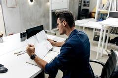 Elegancki ciemnowłosy architekt w szkłach w niebieskiej marynarce i pracuje z dokumentami na biurku w biurze obraz royalty free