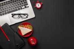 Elegancki czarny biurowy desktop z laptopem, filiżanka kawy i kanapką dla lunchu, Odgórny widok z kopii przestrzenią zdjęcia royalty free