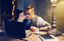 Elegancki dorosły mężczyzna pracuje w domu podczas gdy siedzący przy drewnianym stołem Używać nowożytnego laptop dla badawczych n Fotografia Stock