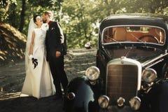 Elegancki elegancki fornal całuje delikatnie wspaniałej panny młodej, przy czarnym ca Fotografia Royalty Free