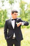 Elegancki elegancki fornal czeka jego spojrzenia przy zegarkiem i brite Zdjęcia Royalty Free