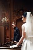 Elegancki elegancki przystojny fornal patrzeje wspaniałej panny młodej, standi Zdjęcie Stock