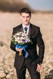 Elegancki elegancki uśmiechnięty potomstwo fornal chodzi samotnie na skalistej plaży z bukietem kwiaty Zdjęcia Stock