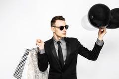Elegancki facet w czarnym kostiumu i okularach przeciwsłonecznych, z torba na zakupy fotografia stock