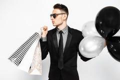 Elegancki facet w okularach przeciwsłonecznych, czarny kostium, trzyma torby, dla robić zakupy zdjęcie stock