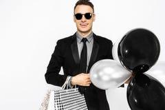 Elegancki facet w okularach przeciwsłonecznych, czarny kostium, trzyma torby, dla robić zakupy obrazy royalty free
