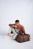 Elegancki faceta obsiadanie na podłoga z podróży torbą Zdjęcia Royalty Free