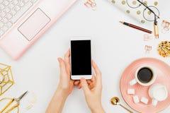 Elegancki flatlay ramowy przygotowania z kobiety ` s wręcza trzymać białego smartphone z czarnym copyspace, różowy laptop, kawa,  Obrazy Stock
