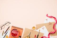 Elegancki flatlay z kopertami, piórem, szkłami, filiżanką herbata i innymi stacjonarnymi akcesoriami, Pojęcie writing listy, zapr fotografia stock