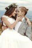 Elegancki fornal niesie szczęśliwej panny młodej i przytulenia, romantyczna oferta Fotografia Stock