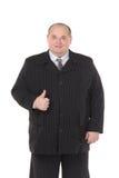 Elegancki gruby mężczyzna w czarnym kostiumu pokazuje kciuk fotografia stock