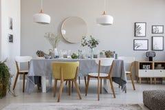 Elegancki jadalni wnętrze z kłaść stołem, krzesłami, lustrem na ścianie i lampami, obraz stock