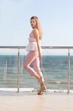 Elegancki kobiety odprowadzenie przy tarasem luksusowy hotel blisko morza Piękna młoda dziewczyna w różowym kostiumu blisko ocean obrazy stock