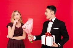 Elegancki mężczyzna, daje prezentowi i bukietowi kwiaty, nierada dziewczyna na czerwonym tle, zdjęcia royalty free