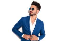 Elegancki mężczyzna jest ubranym okulary przeciwsłonecznych zapina jego spojrzenia i kostium daleko od zdjęcia royalty free