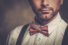 Elegancki mężczyzna jest ubranym suspenders i pozuje na ciemnym tle z łęku krawatem obrazy stock