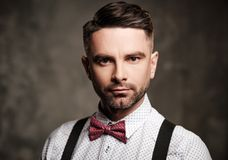 Elegancki mężczyzna jest ubranym suspenders i pozuje na ciemnym tle z łęku krawatem zdjęcia stock