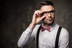 Elegancki mężczyzna jest ubranym suspenders i pozuje na ciemnym tle z łęku krawatem obraz royalty free