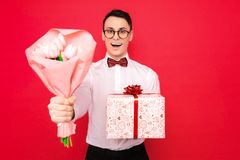 Elegancki mężczyzna, jest ubranym szkła, z prezentem i bukietem kwiaty, na czerwonym tle pojęcie kobieta dzień zdjęcia royalty free