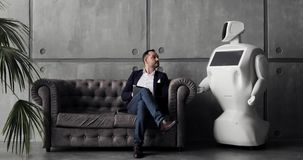 Elegancki mężczyzna komunikuje z robotem, naciska plastikową machinalną rękę robot, uścisk dłoni Cybernetyczny system zbiory wideo