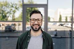 Elegancki mężczyzna ono uśmiecha się przy kamerą i pozycją przy budynkiem biurowym zdjęcie stock