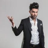 Elegancki mężczyzna trzyma jeden rękę w powietrzu w smokingu Fotografia Royalty Free
