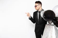 Elegancki mężczyzna w czarnym kostiumu z torbami w jego rękach i piłce, obrazy royalty free